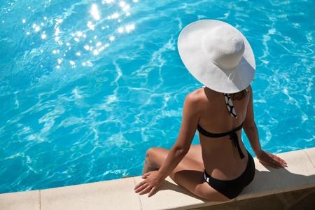 leasure: Giovane donna seduta sulla Cengia della piscina.