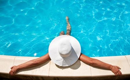 meisje zwemmen: Jonge vrouw zitten op de richel van het zwembad.