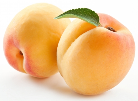 Two ripe apricot with a leaf on a white background.