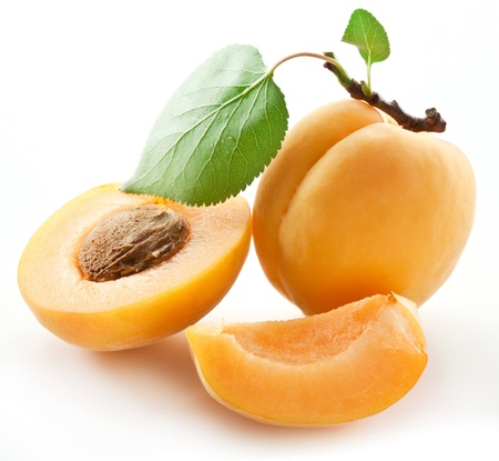 Apricots with leaves on a white background. Stock Photo