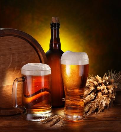Bodegón con un barril de cerveza y cerveza de proyecto por el vidrio.
