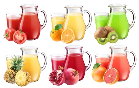 Collection of fresh juices in pitchers. Nearby are the ingredients of juices. Stock Photo