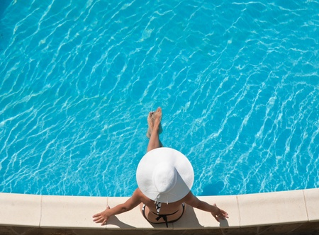 leasure: Young woman sitting on the ledge of the pool.