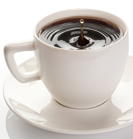 Splash in coffee cup. Isolated on a white background. photo