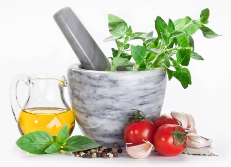peper: Mortar with pestle and basil herbs and olive oil.