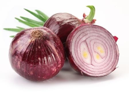 onions: Los bulbos de cebolla roja con hojas verdes sobre un fondo blanco. Foto de archivo