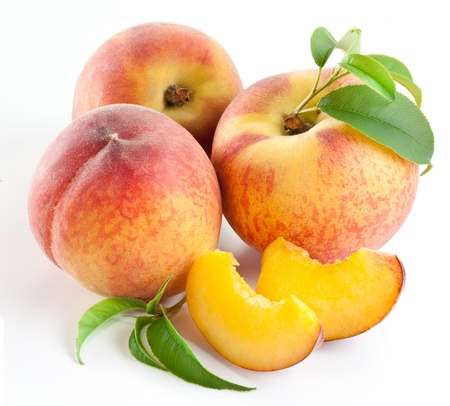 Ripe peach fruit with leaves and slises on white background. Imagens