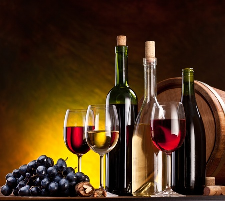Still life with wine bottles, glasses and oak barrels.  Stock Photo - 10892304