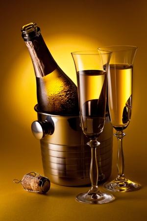 Botella de champagne en el refrigerador y dos copas de champán. Sobre un fondo amarillo.