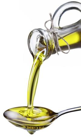 aceite de cocina: El aceite de oliva vierte de una botella en una cuchara de metal. Imagen aislada sobre un fondo blanco.
