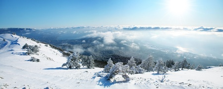 snowy mountain: Beautiful winter panorama. View from the mountains to the sea above the clouds. Stock Photo