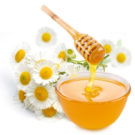 Honey pours with sticks in a jar. Flowers are near. Isolated on white background. Stock Photo - 10978531