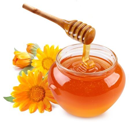 honey jar: Honey pours with sticks in a jar. Flowers are near. Isolated on white background.