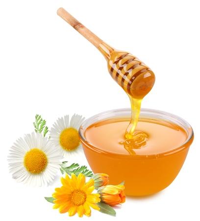 Honing giet met stokken in een pot. Bloemen zijn in de buurt. Geà ¯ soleerd op witte achtergrond. Stockfoto