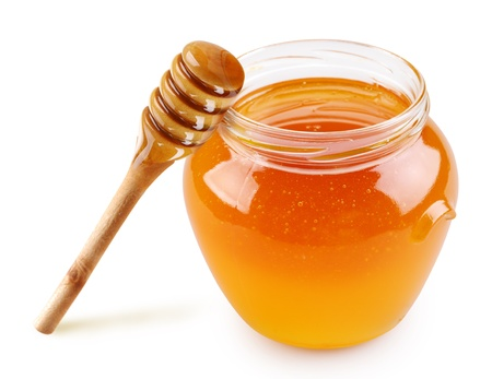a jar stand: Honey in a glass jar with a stick on a white background.
