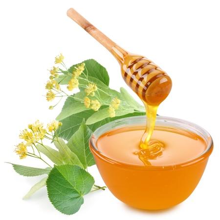 tilo: Linden miel est� vertiendo con palos en un frasco. Junto a ellos est�n las flores de tilo. Aisladas sobre fondo blanco.
