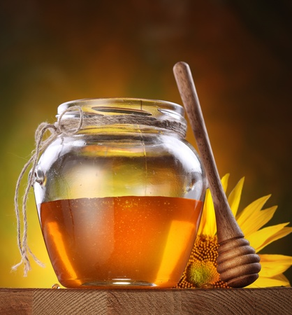 a jar stand: Honey in a glass jar and flower sunflower on a wooden table.