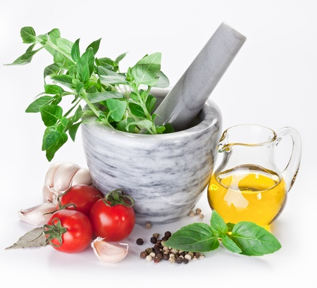Mortar with pestle and basil herbs and olive oil. Stock Photo - 11373557
