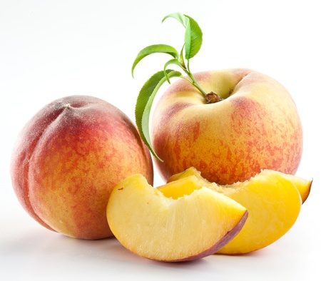 Ripe peach fruit with leaves and slises on white background. Stockfoto