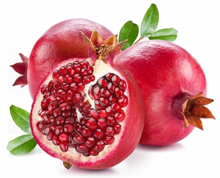 Ripe pomegranates with leaves isolated on a white background.