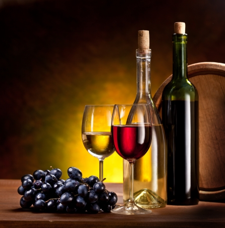 wine and grapes: Still life with wine bottles, glasses and oak barrels   Stock Photo
