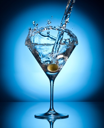 vermouth: Splash martini from flying olives. Object on a blue background. Stock Photo