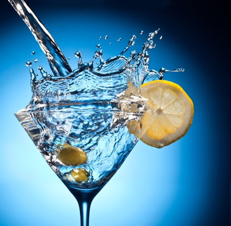 gin: Splash from pouring martini into the glass. Object on a blue background. Stock Photo