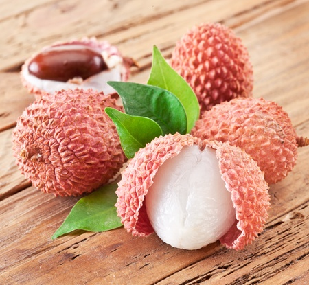 litchee: Lychee with leaves on a wooden table  Stock Photo