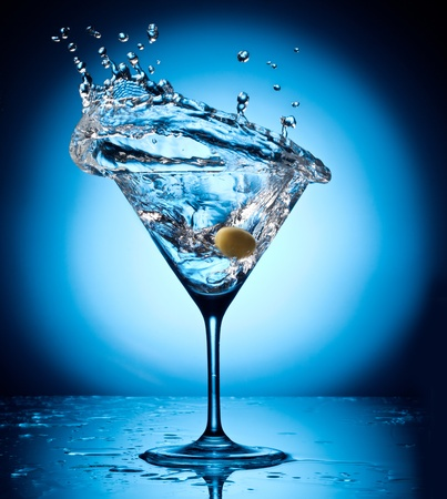 Splash martini from flying olives  Object on a blue background