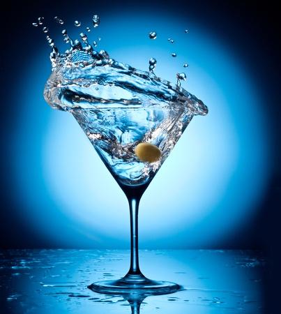 copa de martini: Splash martini del objeto volador aceitunas en un fondo azul Foto de archivo