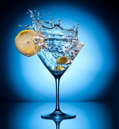 martini splash: Splash martini from flying olives  Object on a blue background