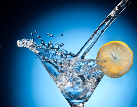 martini splash: Splash from pouring martini into the glass  Object on a blue background  Stock Photo