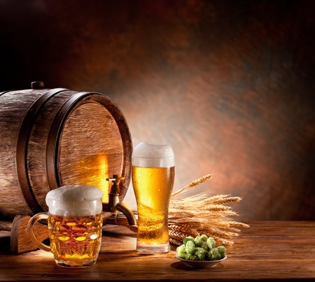 mug of ale: Beer barrel with beer glasses on a wooden table  The dark background