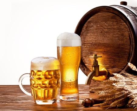 vasos de cerveza: Barril de cerveza con vasos de cerveza en una mesa de madera aislada sobre un fondo blanco