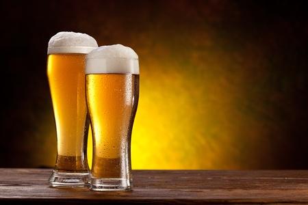 Dwie szklanki piwa na drewnianym stole ciemnym tle żółtym