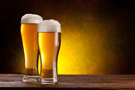 pub: Two glasses of beers on a wooden table  Dark yellow background