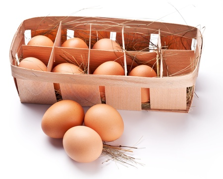 eier: Eier mit einem Strohhalm in einem h�lzernen Korb auf einem wei�en Hintergrund