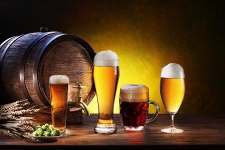 Bierfass mit Biergläsern auf einem Holztisch Der dunkle Hintergrund