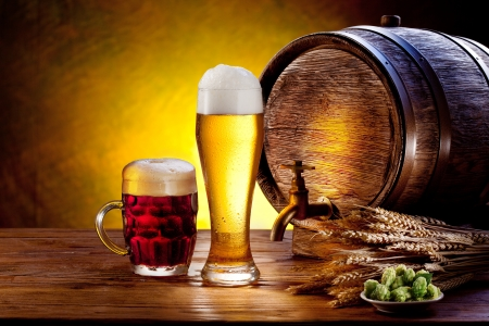 still life: Beer barrel with beer glasses on a wooden table  The dark background