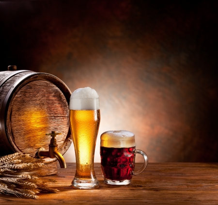 brewing: Beer barrel with beer glasses on a wooden table  The dark background