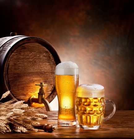 beer drinking: Beer barrel with beer glasses on a wooden table  The dark background