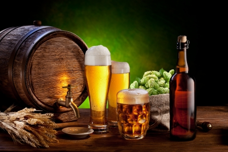 mug of ale: Beer barrel with beer glasses on a wooden table  The dark green background  Stock Photo