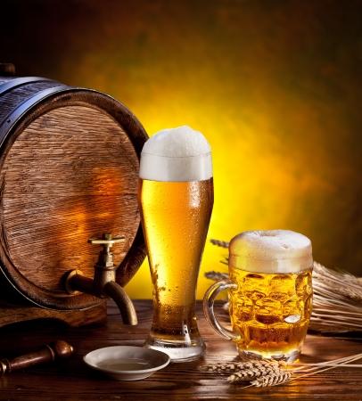 vasos de cerveza: Cerveza barril con vasos de cerveza en una mesa de madera del fondo oscuro Foto de archivo
