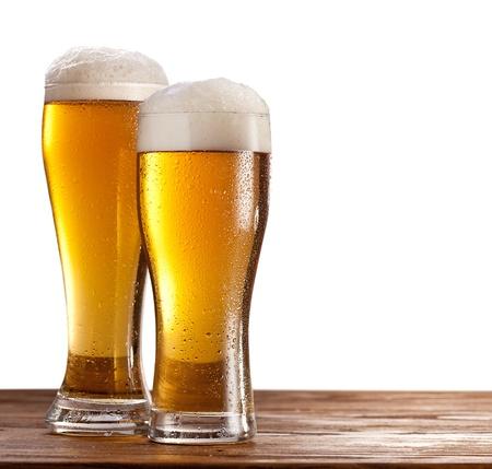 vasos de cerveza: Dos vasos de cervezas en una mesa de madera aislado en un fondo blanco Foto de archivo