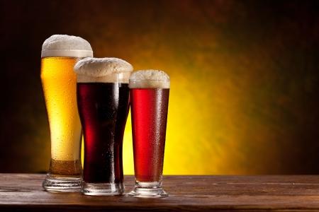 grifos: Cerveza barril con vasos de cerveza en una mesa de madera del fondo oscuro Foto de archivo