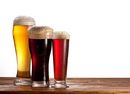 grifos: Tres vasos de cervezas diferentes en una mesa de madera aislado en blanco Foto de archivo