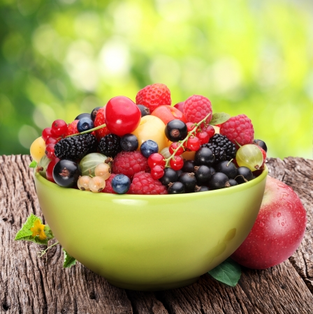 Bowl with a variety of berries on the old wooden table. Against the backdrop of summer foliage.