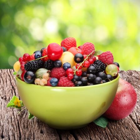 ciotola: Ciotola con una variet� di frutti di bosco sul tavolo in legno vecchio. Sullo sfondo di fogliame di estate. Archivio Fotografico
