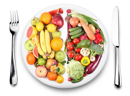Frutas y verduras están en lados opuestos de la placa. Iimage sobre fondo blanco.