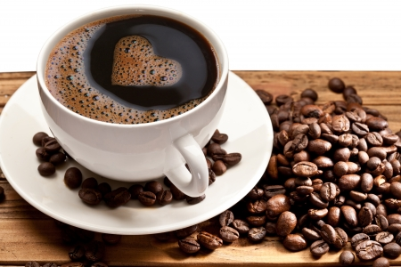 decaf: Coffee cup and saucer on a wooden table. Foam in the form of the heart. Stock Photo